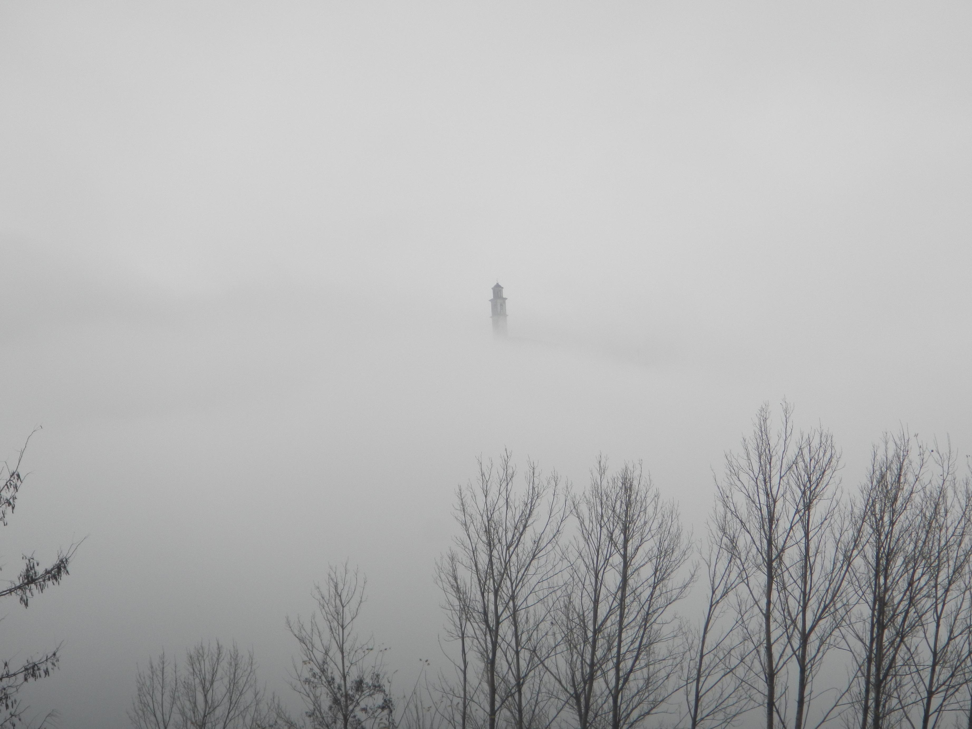 Un campanile svetta nella nebbia